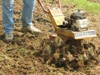 A motorized tiller breaking up soil.