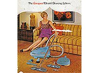 50s-era ad of woman sitting on striped couch holding the end of a vacuum cleaner.
