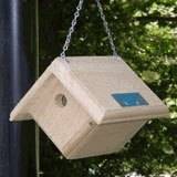 A wooden birdhouse hanging outdoors.