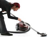 A woman vacuuming.