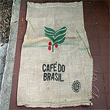 "A coffee burlap bag with the writing ""Cafe Do Brasil"" on it."