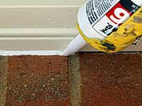 Caulking between trim and brick on the outside of a house.