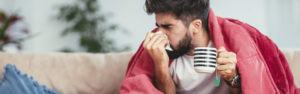 Man blowing his nose while sitting sick on the couch.